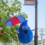 The Rain Day Mascot, Wayne Drop, posing on High Street with an umbrella