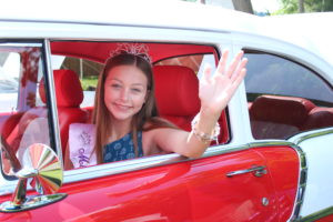Miss Rain Day posing in a car at the Freedom Car Show